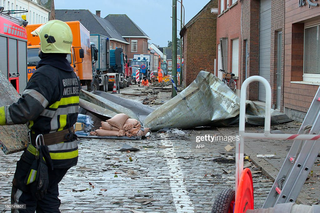 A firefighter stands in a street damaged by a whirlwind in the village of Oosterzele, East-Flanders, on February 5, 2013. SCHEIRE -Belgium Out-