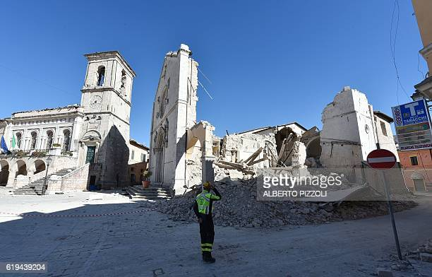 TOPSHOT A firefighter stands in front of the destroyed Basilica of St Benedict in the historic center of Norcia on October 31 a day after a 66...