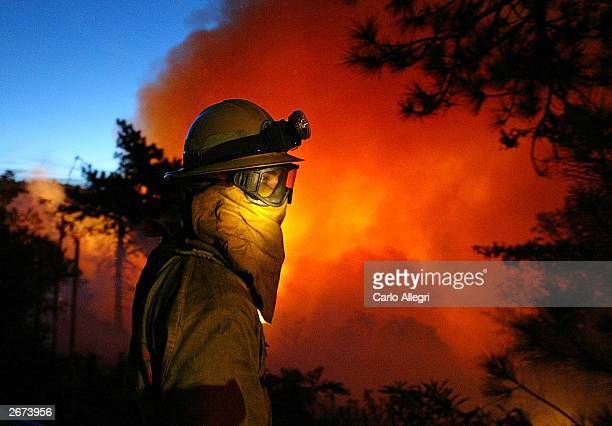 A firefighter stands in front of the flames as the struggle to get the Crestline Wildfire under control continues overnight in Los Angeles County...