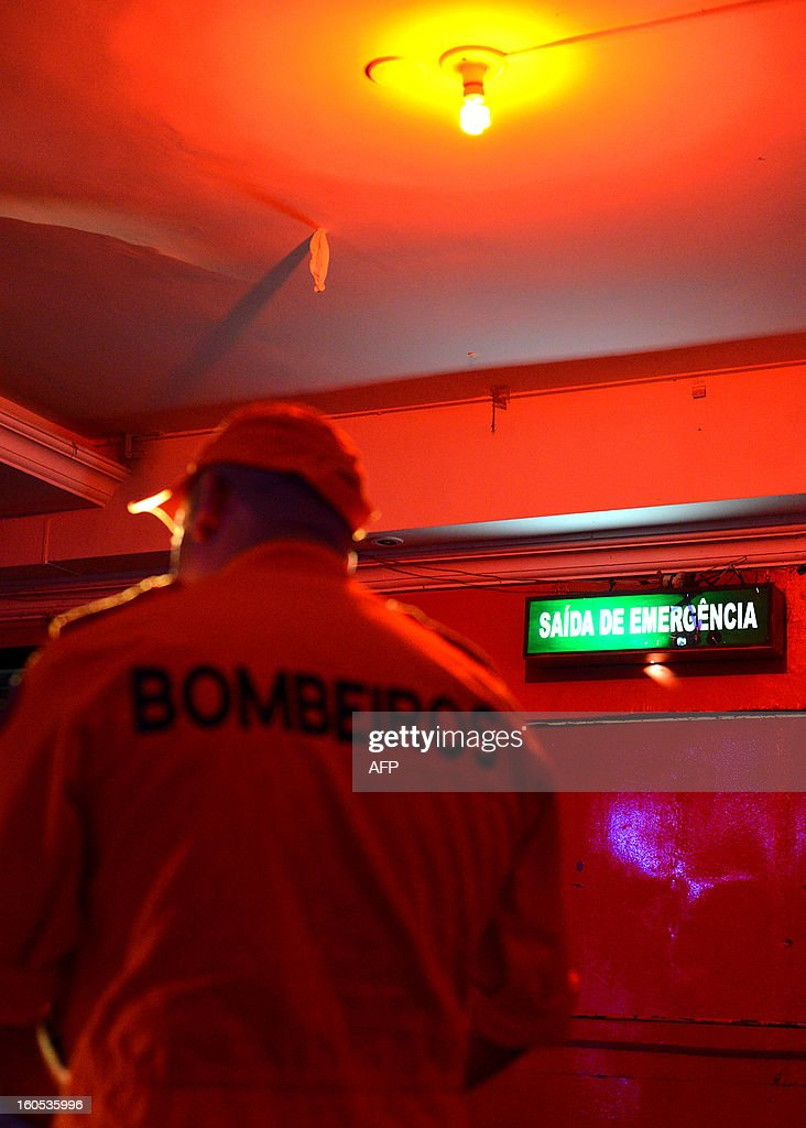 A firefighter stands next to an emergency exit during an inspection to a nightclub in a suburb of Brasilia, on February 2, 2013. The Brazilian authorities ordered the inspection of many bars and nightclubs all over the country after the blaze in the Kiss Nightclub in Santa Maria, southern Brazil, that left more than 230 people dead. AFP PHOTO/ Pedro LADEIRA