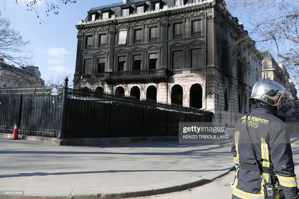 A firefighter stands on February 21, 2013 outside the Paris nightclub and restaurant L'Arc after a fire, believed to have been set by arsonists, swept through it in the early morning.