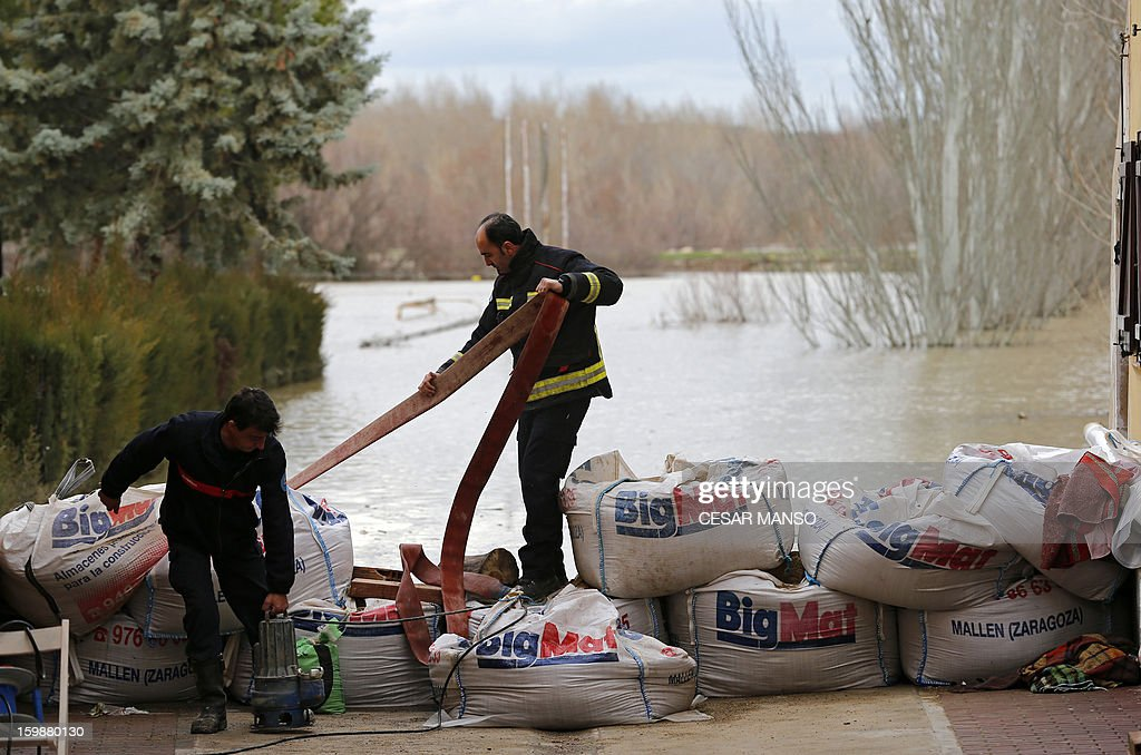 A firefighter stands on sacks of sand in a street of Novillas, near Zaragoza, following the rise ot the River Ebro on January 22, 2013.