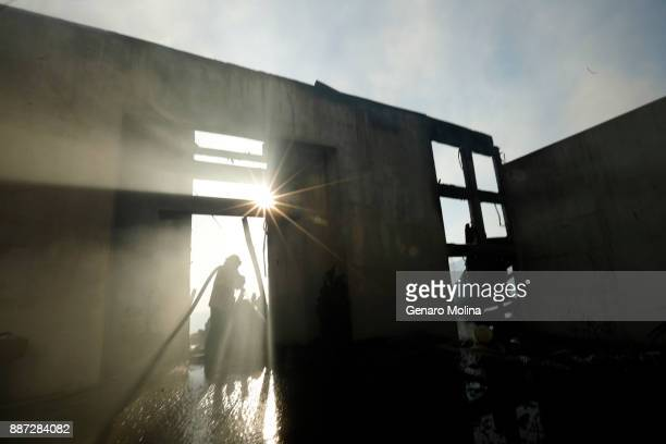 BEL AIR DECEMBER 6 2017 Firefighter Steve Barrett hits a hot spot on a fire ravaged home at 1211 Linda Flora Drive in Bel Air on December 6 2017