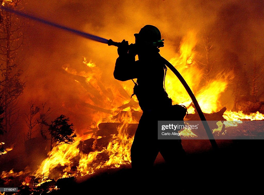 A firefighter struggles to battle the Crestline Wildfire that has swept through the area in Los Angeles County October 28, 2003 near Los Angeles, California. The wildfires have burned over 300,000 acres devouring more than 600 homes and taking at least 13 lives.