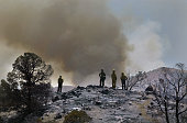 Firefighter supervisors watch as smoke rises in the hills of Acton facing east as they try to determine how the wind and fire activity will go from...