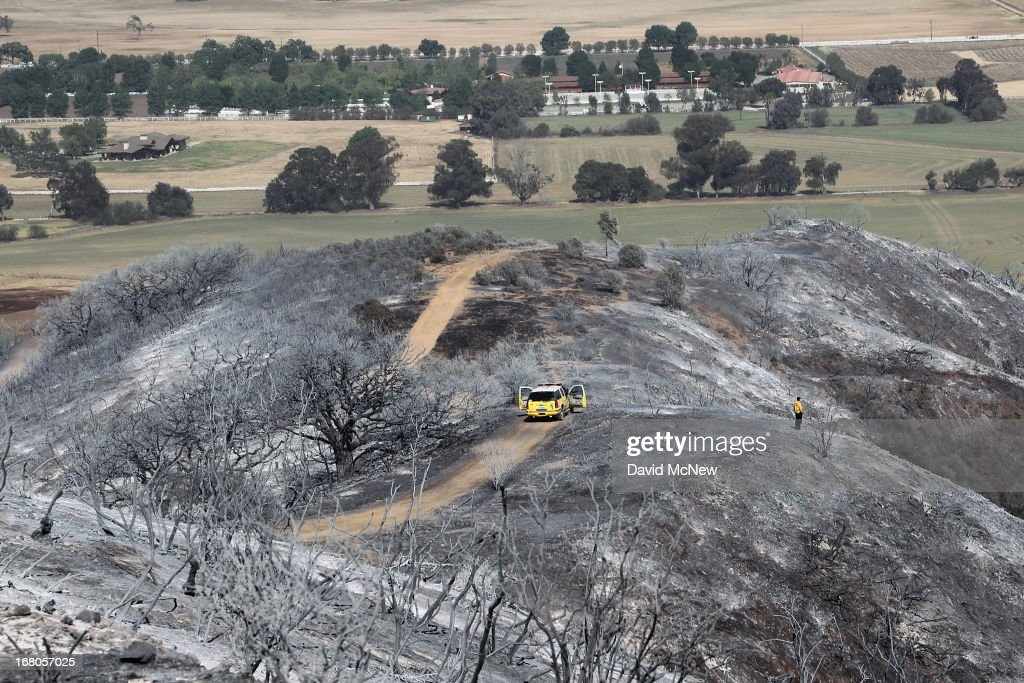 A firefighter surveys burned hills near Hidden Valley at the Springs fire on May 4, 2013 near Camarillo, California. Improving weather conditions are helping firefighters get the upper hand on the wildfire which has grown to 28,000 acres and is now 56 percent contained.