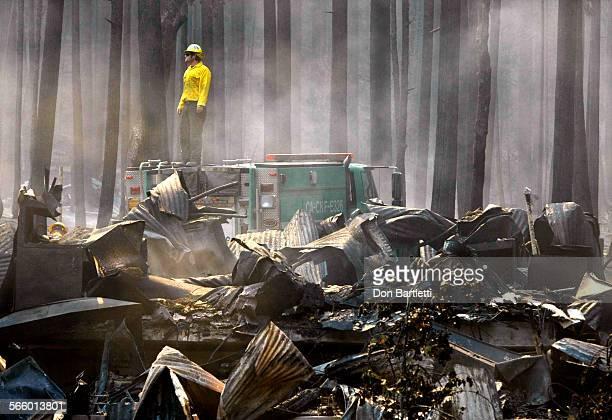 AUGUST 26 2013 GROVELAND CA A firefighter surveys the smoldering ruins of The Berkeley Tuolumne Camp near Groveland CA on Aug 26 2013 The 1922...