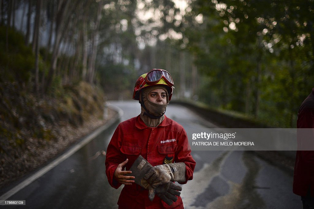A firefighter takes off her gloves after fighting a wildfire in Caramulo, central Portugal, on August 30, 2013. Firefighters battled wildfires on August 30 in Portugal where they have claimed five lives and tamed another major blaze in northern Spain, officials said. In Portugal, some 1,400 firefighters backed by Spanish and French aircraft were battling a series of fires that have ravaged thousands of hectares of forest in the north and centre of the country.