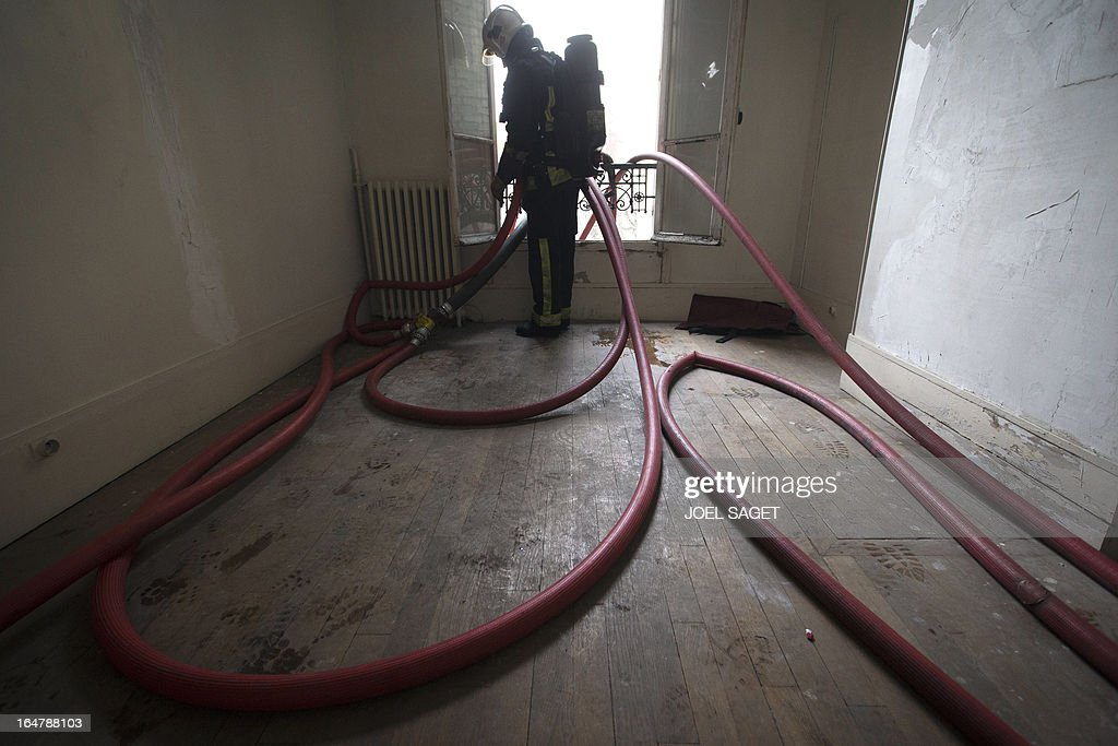 A firefighter takes part in an exercise on March 28, 2013 in Paris, focused on benefits of smoke detectors. AFP PHOTO / JOEL SAGET