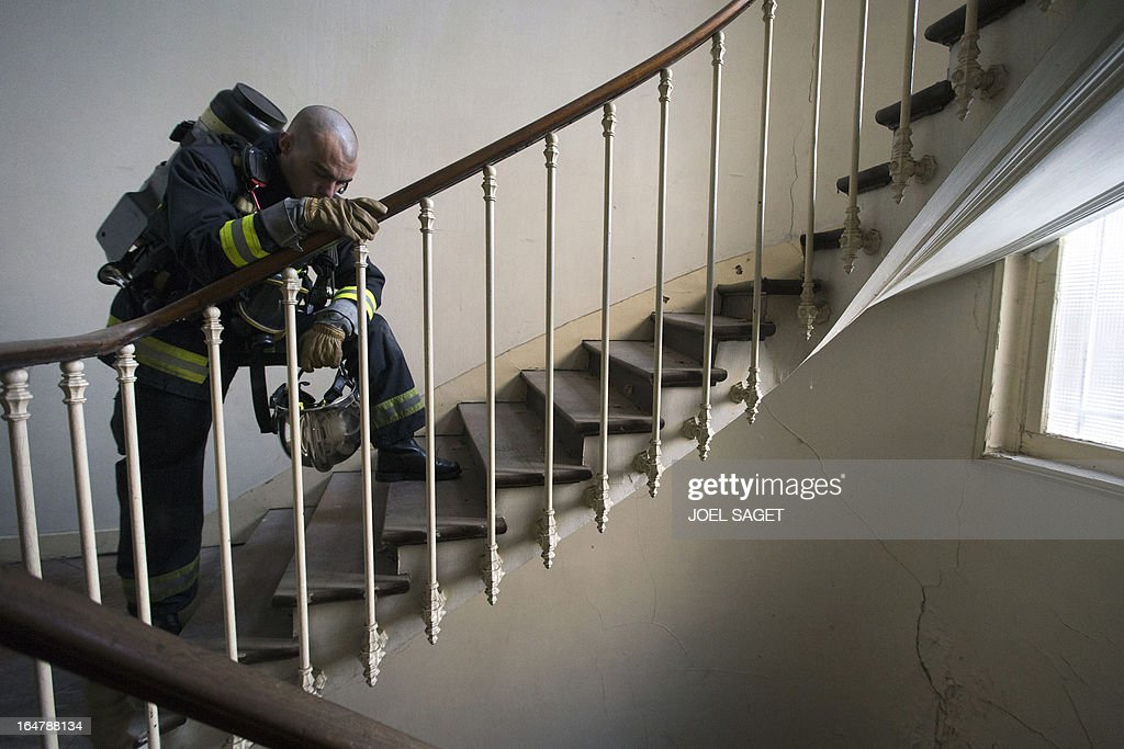 A firefighter takes part in an exercise on March 28, 2013 in Paris, focused on benefits of smoke detectors.