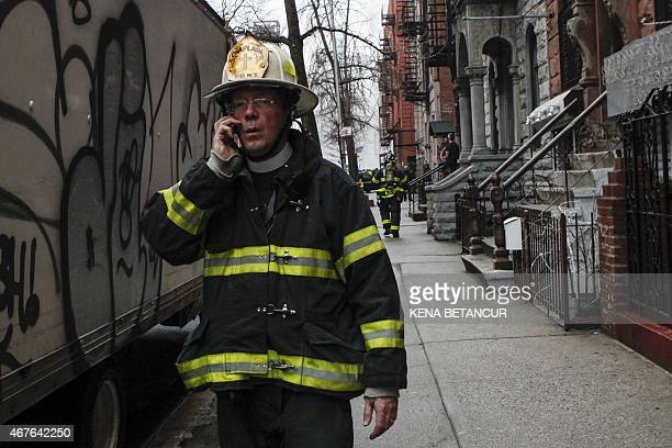 A firefighter talks on a phone near a blaze at a commercial and residential block on March 26 in New York's East Village The entire building at 125...