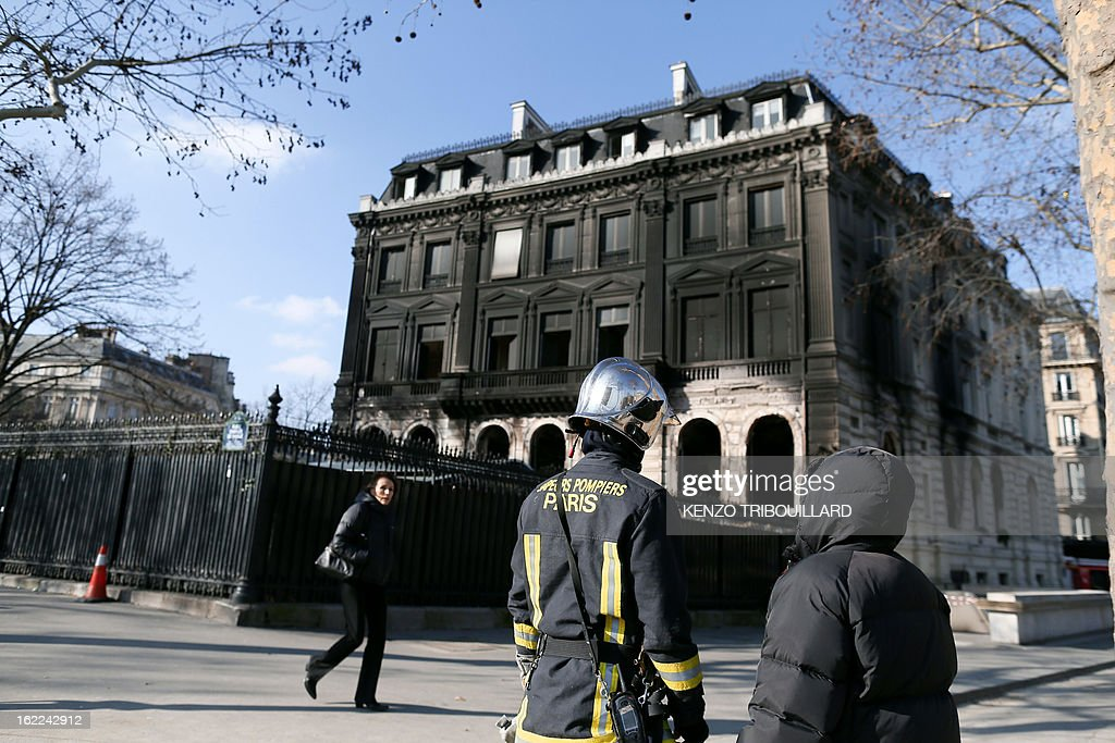 A firefighter talks on February 21, 2013 with a passers-by outside the Paris nightclub and restaurant L'Arc after a fire, believed to have been set by arsonists, swept through it in the early morning. AFP PHOTO / KENZO TRIBOUILLARD