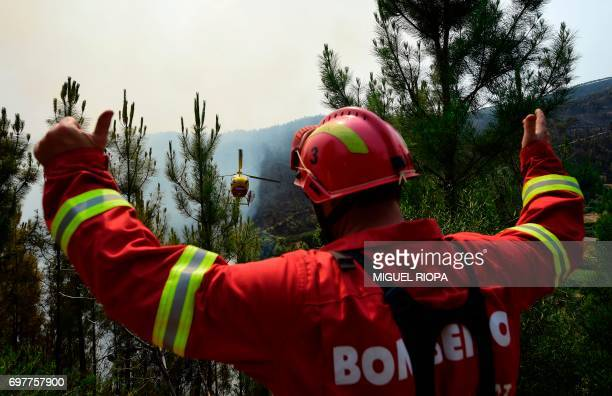 A firefighter thumbs up as a helicopter drops water over a wildfire in Carvalho next to Pampilhosa da Serra on June 19 2017 More than 1000...
