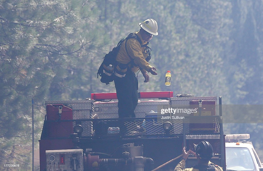 A firefighter tosses a bottle of Gatorade to a colleague while taking a break from battling the Rim Fire on August 22, 2013 in Groveland, California. The Rim Fire continues to burn out of control and threatens 2,500 homes outside of Yosemite National Park. Over 1,000 firefighters are battling the blaze that was reduced to only 2 percent containment after it nearly tripled in size overnight.
