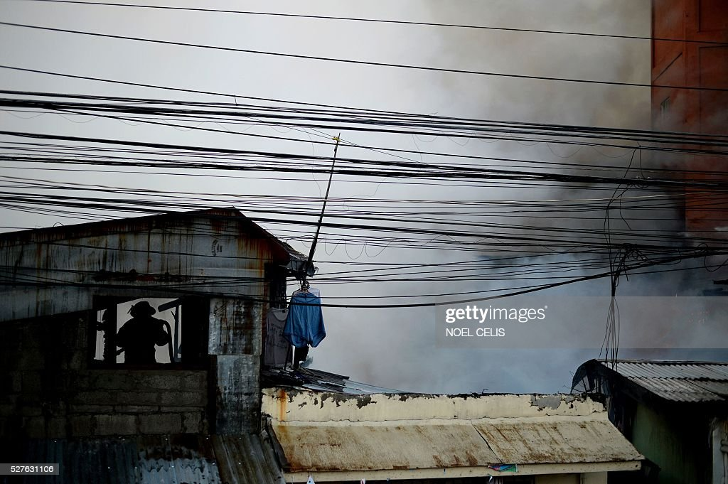 A firefighter tries to put out a fire that swept over several houses in a residential area in Manila on May 3, 2016. No one was hurt in the fire, according to initial reports. / AFP / NOEL