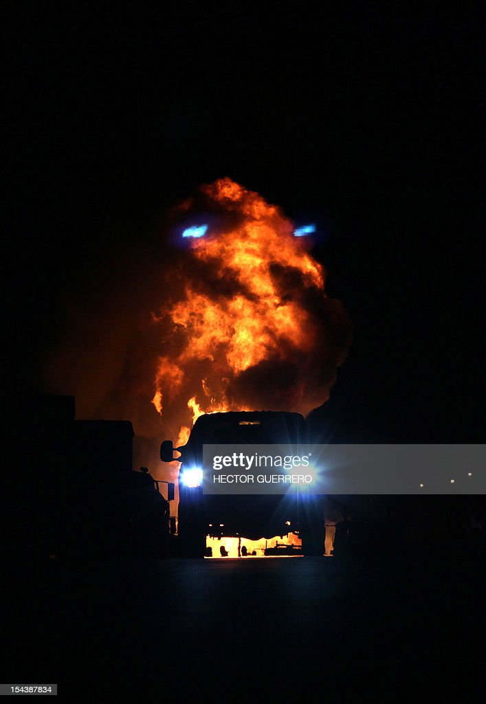 A firefighter truck circulates next to flames caused by the explosion of a gas pipeline in Zapotlanejo, 30 km from Guadalajara city, Jalisco State, Mexico on October 19, 2012. The explosion injured two people and forced the evacuation of 600 residents, according to local authorities. AFP PHOTO/Hector Guerrero