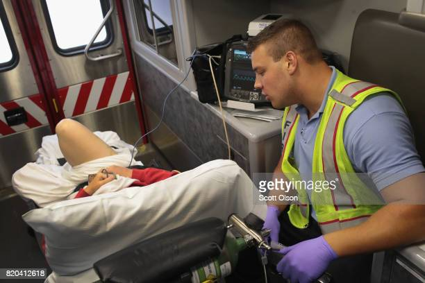 Firefighter Tyler Behrends treats an overdose victim as she is transported to a hospital on July 14 2017 in Rockford Illinois The woman was found on...