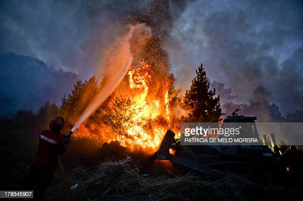 A firefighter uses a hose as a bulldozer pushes earth onto a wildfire in Caramulo central Portugal on August 29 2013 Five Portuguese mountain...