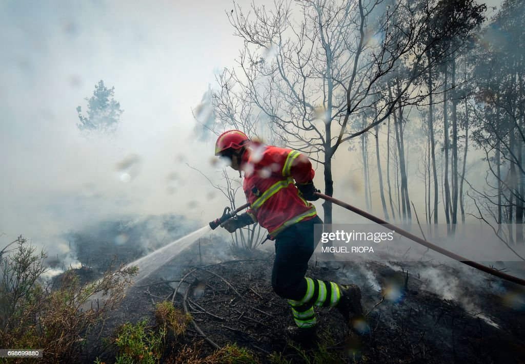 TOPSHOT - A firefighter uses a hose to combat a wildfire in Vale da Ponte, Pedrograo Grande, on June 20, 2017. The huge forest fire that erupted on June 17, 2017 in central Portugal killed at least 64 people and injured 135 more, with many trapped in their cars by the flames. RIOPA