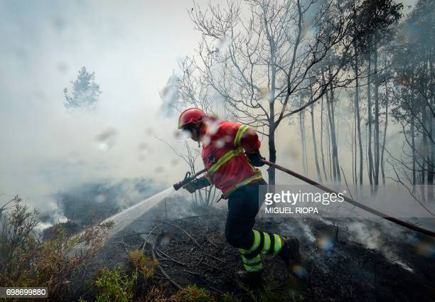 TOPSHOT A firefighter uses a hose to combat a wildfire in Vale da Ponte Pedrograo Grande on June 20 2017 The huge forest fire that erupted on June 17...