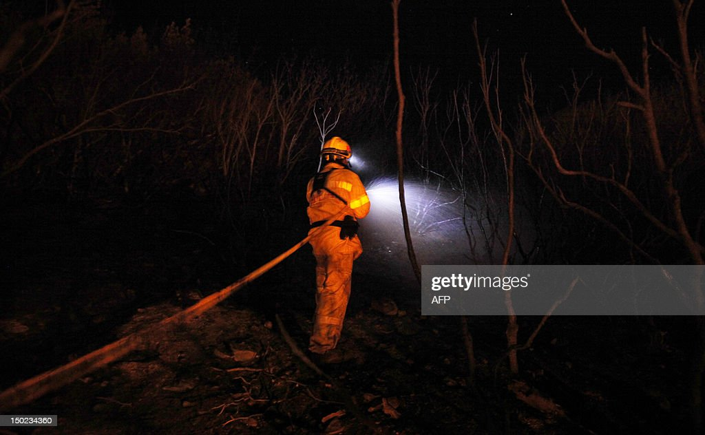 A firefighter uses a hose to spray water in the National Park of Garajonay, after 9 days of forest fires on the Spanish Canary island of La Gomera on August 13, 2012. Scores of villagers spent the night in hotels and student halls after fleeing wildfires that continued raging out of control on August 12 on the Spanish Canary Islands. AFP PHOTO / Desiree Martin