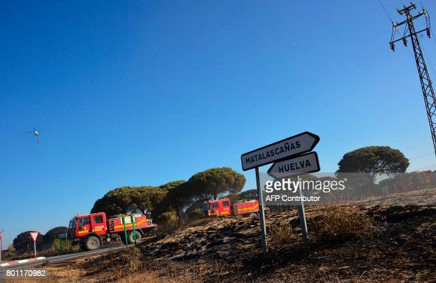 Firefighter vehicle pass by a burned area after a wildfire in Mazagon near the Donana National Park on June 26 2017 More than 1500 people were...