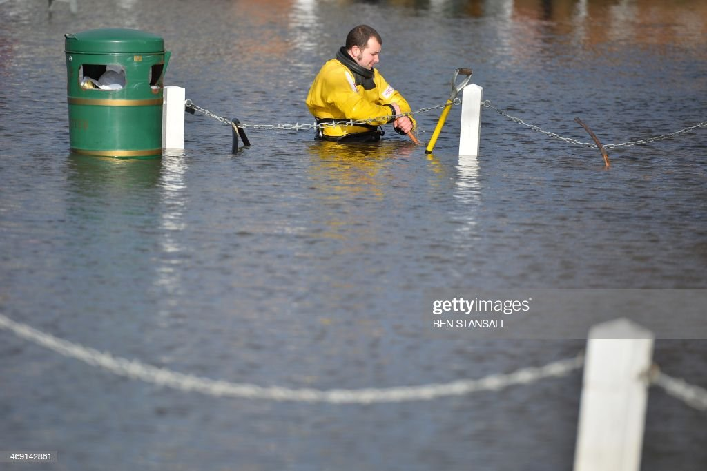A Firefighter wades through chest high water in the flooded village of Datchet, west of London, on February 13, 2014. Hurricane-force winds from an Atlantic storm left tens of thousands of Britons without power Thursday and one man dead, adding to the misery after devastating floods caused by the wettest winter in 250 years.