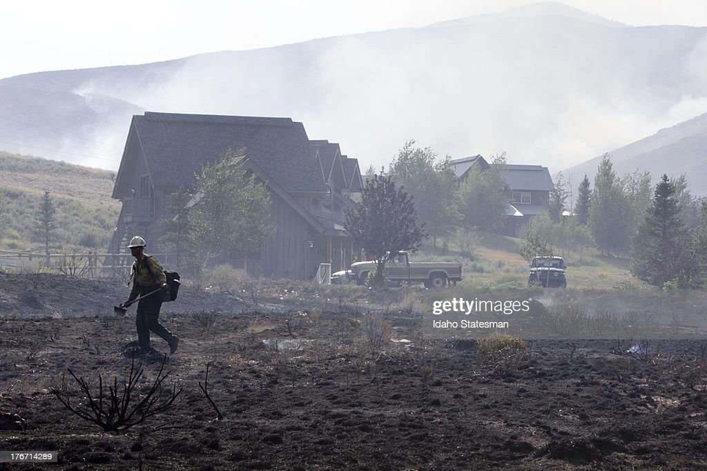 A firefighter walks across a blackened field near homes on Croy Road and the Rotorun ski hill west of Hailey, Idaho, Saturday, August 17, 2013. The Beaver Creek fire moved through the area in the early hours Saturday morning