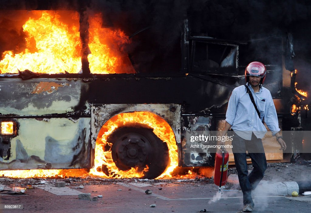 A firefighter walks away from a bus torched by supporters of former Prime Minister Thaksin Shinawatra during a protest on April 13, 2009 in Bangkok, Thailand. Anti-government protesters clashed with the military on the streets of Thailand's capital after the government declared a state of emergency. The pro-Shinawatra demonstrators are calling for the resignation of Prime Minister Abhisit Vejjajiva and for fresh elections to be held.