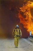 A firefighter walks away from large flames from the Crown fire in the hills around the Angeles Forest Highway near Palmdale The fire started closer...