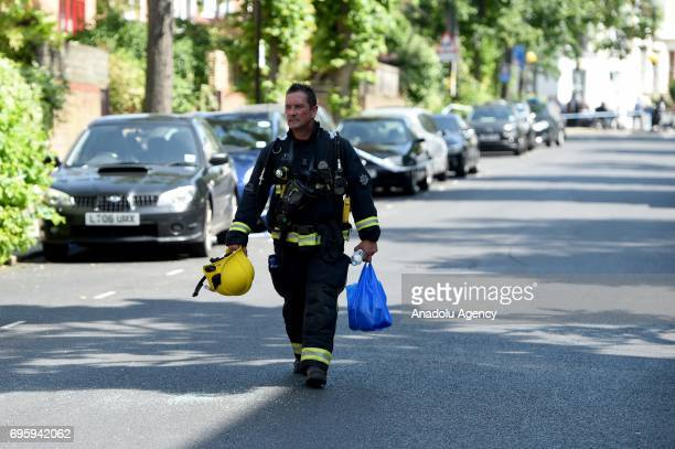 Firefighter walks down the street with supplies after a huge fire engulfed the 24 storey residential Grenfell Tower block in Latimer Road West London...