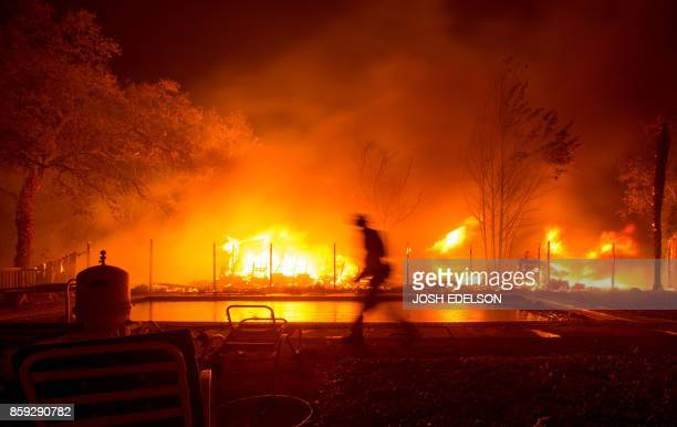 TOPSHOT A firefighter walks near a pool as a neighboring home burns in the Napa wine region in California on October 9 as multiple winddriven fires...
