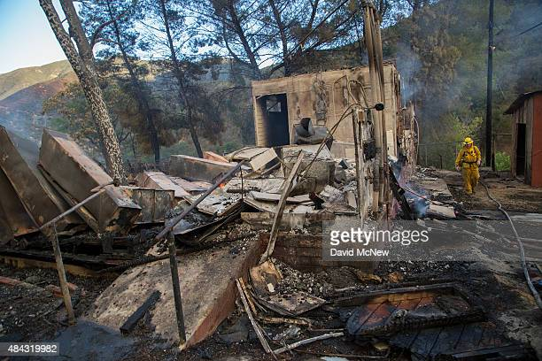A firefighter walks near the ruins of a burned building at the Warm Springs Rehabilitation Center at the Warm Fire on August 16 2015 in the Angeles...