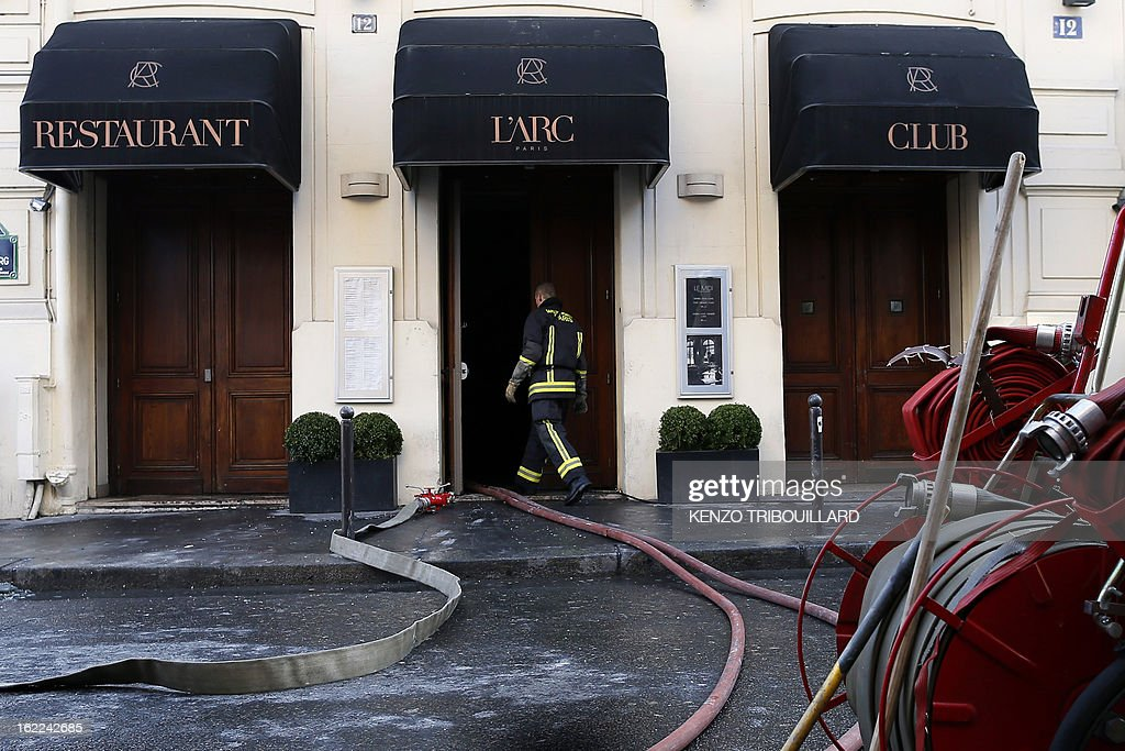 A firefighter walks on February 21, 2013 into the restaurant of the Paris nightclub L'Arc after a fire, believed to have been set by arsonists, swept through it in the early morning.