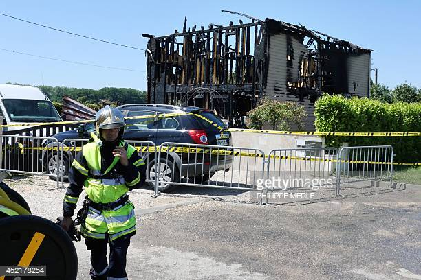 A firefighter walks on July 15 2014 by the house where a 16 year old boy and two girls aged 8 and 11 died during the night of July 14 to July 15 in a...