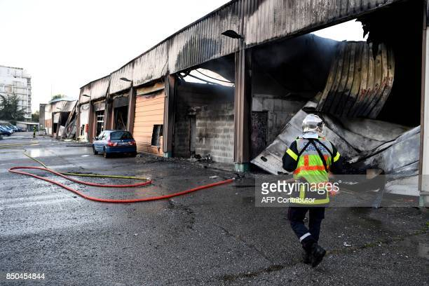 A firefighter walks on September 21 2017 in Grenoble eastern France past on a burntout garage which contained about fifty vehicles of the French...