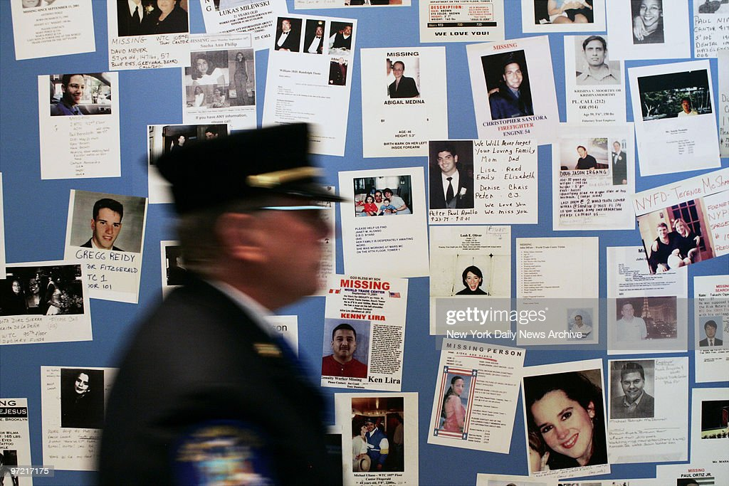 A firefighter walks past a wall of missing persons posters d