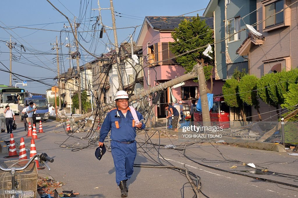 A firefighter walks past downed electricity cables and poles along a street after a tornado tore though Koshigaya in Saitama prefecture, suburban Tokyo on September 2, 2013. Several dozen people were injured when a tornado ripped through parts of eastern Japan, tearing off roofs and uprooting buildings. AFP PHOTO / Yoshikazu TSUNO