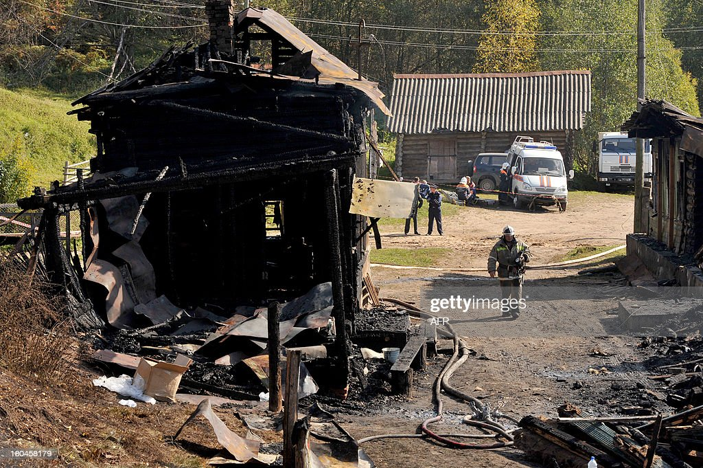 A firefighter walks past the charring remains of a burned out psychiatric hospital in the village of Luka in the northwest Russian Novgorod region on September 13, 2013. Thirty seven people were killed when a fire swept through a wooden psychiatric hospital in northwest Russia overnight yesterday, regional investigators said.