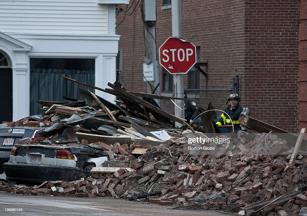 A firefighter walks past two cars buried in bricks on the backside of the building where two firefighters were injured fighting last nights fire, which destroyed one of the oldest buildings in Leominster on Main Street, Sunday, Nov. 25, 2012. The building was a former hotel that housed apartments and businesses.