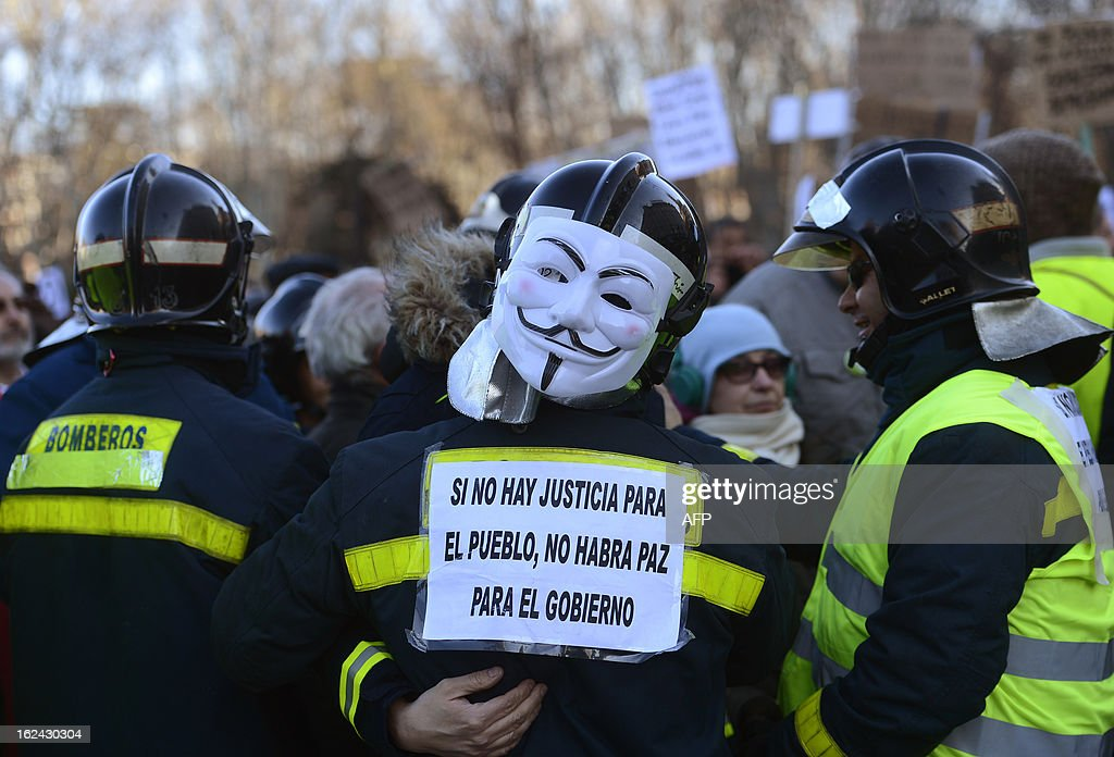A firefighter wearing a Guy Fawkes mask and holding a placard reading 'If there is no justice for the people, there will be no peace for the government' attends a demonstration by public workers, small political parties and non-profit organisations against government austerity on February 23, 2013 in Madrid. Nurses, doctors, students, miners and members of Spain's 'indignant' movement against economic inequality join in the so-called 'citizens' tide' against the steep spending cuts and tax hikes imposed by Prime Minister Mariano Rajoy's conservative government to slash the public deficit. The day of protest coincides with the 31st anniversary of the failure of right-wing military coup that sought to crush Spain's young democracy and restore military rule. AFP PHOTO / PIERRE-PHILIPPE MARCOU