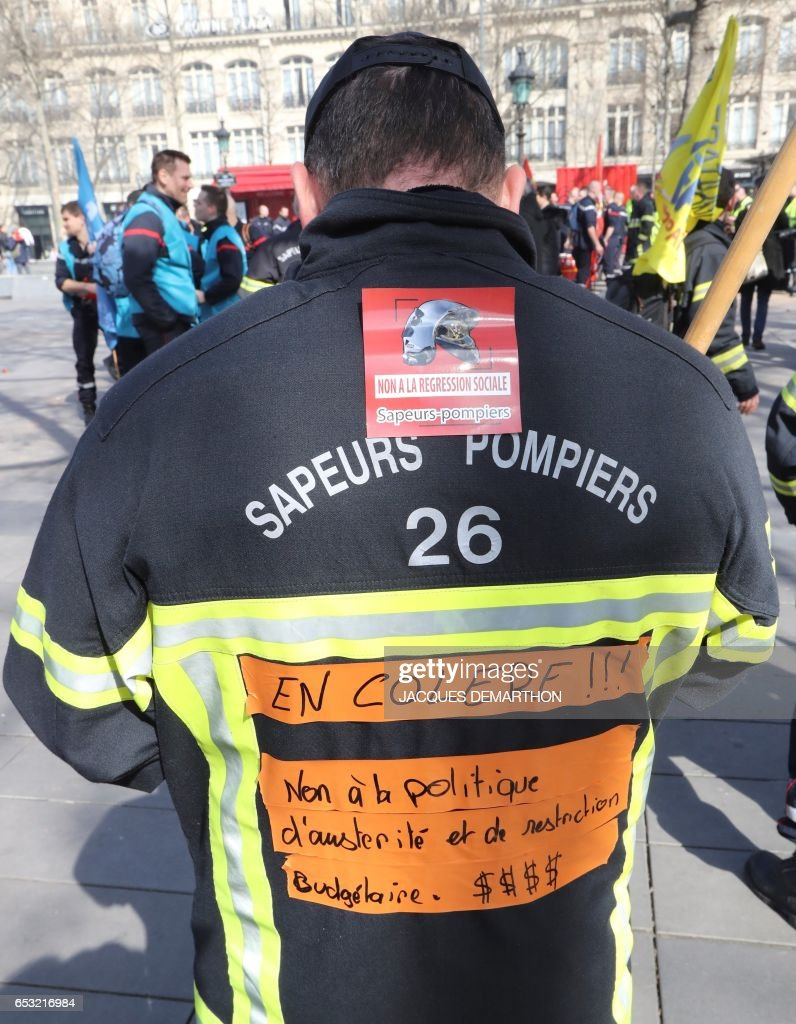 A firefighter wears a jacket with a writing reading 'Angry ! Stop the austerity and restriction politics' during a demonstration of French firemen against staff reduction on the place de la Republique in Paris on March 14, 2017. / AFP PHOTO / Jacques DEMARTHON