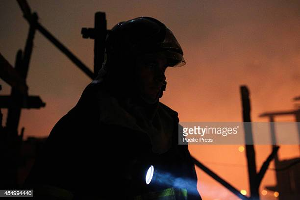 A firefighter with a flashlight looks on as a major fire struck a slum located in the Campo Belo neighborhood on the Journalista Roberto Marinho...
