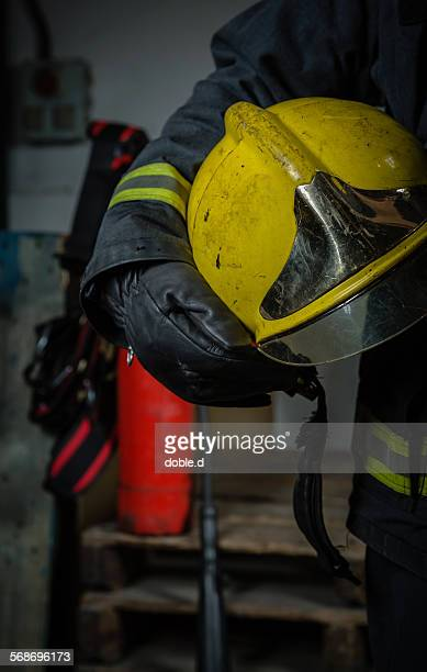 Firefighter with equipment holding security helmet