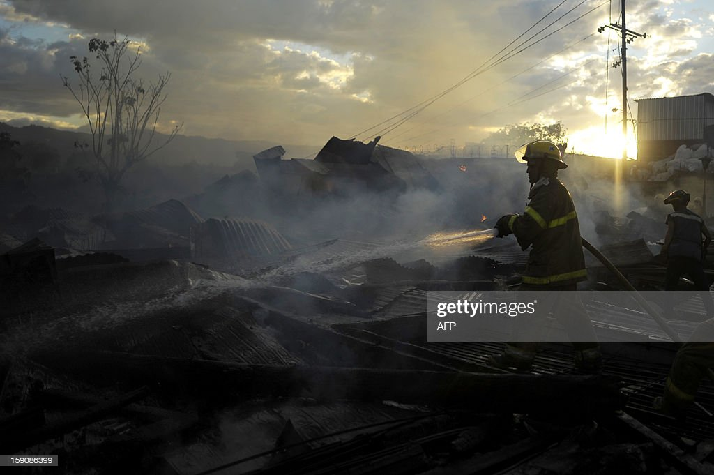 A firefighter works amid smouldering rubble following a blaze that destroyed the San Esteban Church, an historical landmark in downtown San Salvador, El Salvador on January 7, 2012. The San Esteban was built in the 19th century in Belgium, transported and assembled in one of the oldest neigborhoods of the capital city. AFP PHOTO/ Jose CABEZAS
