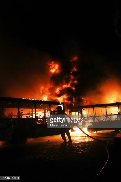 A firefighter works as buses burn after being set on fire by protestors during a nationwide general strike on April 28 2017 in Rio de Janeiro Brazil...