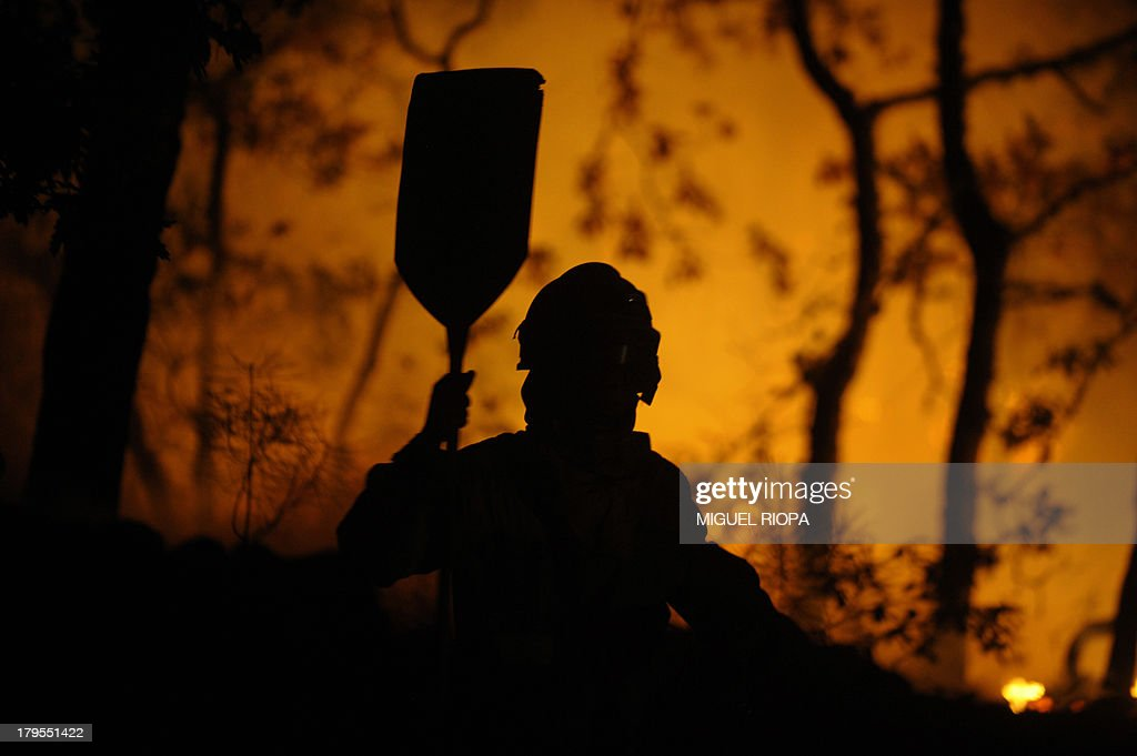 A firefighter works at the site of a wildfire in the village of Barbudo, some 40 km from Vigo, northwestern Spain, in the early hours of September 5, 2013. AFP PHOTO/ MIGUEL RIOPA