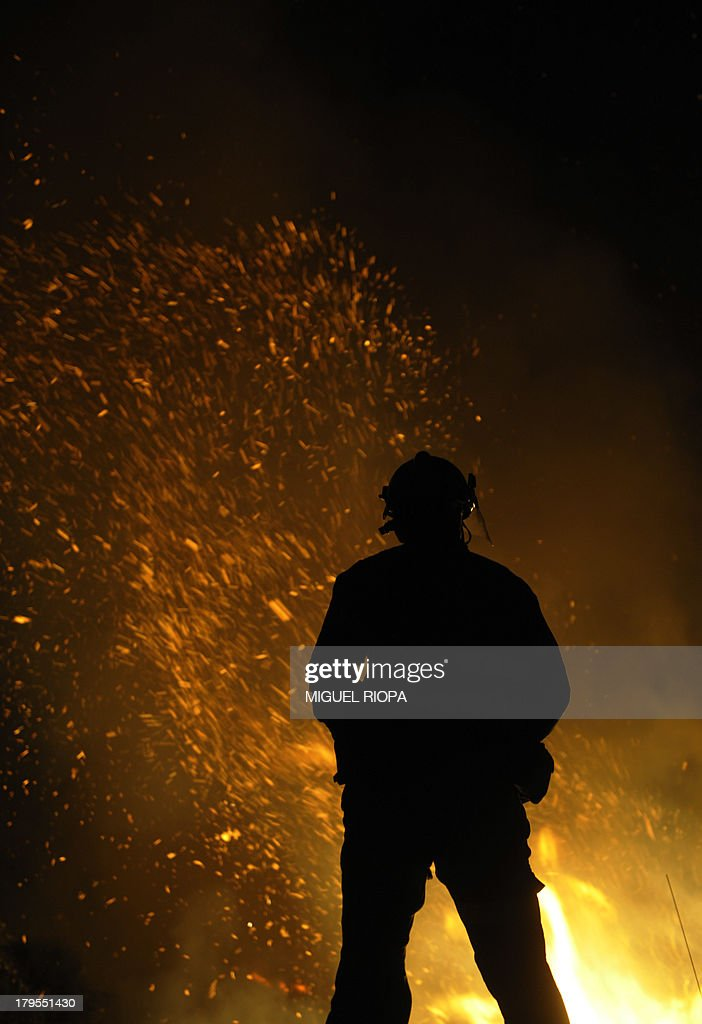 A firefighter works at the site of a wildfire in the village of Barbudo, some 40 km from Vigo, northwestern Spain, in the early hours of September 5, 2013.