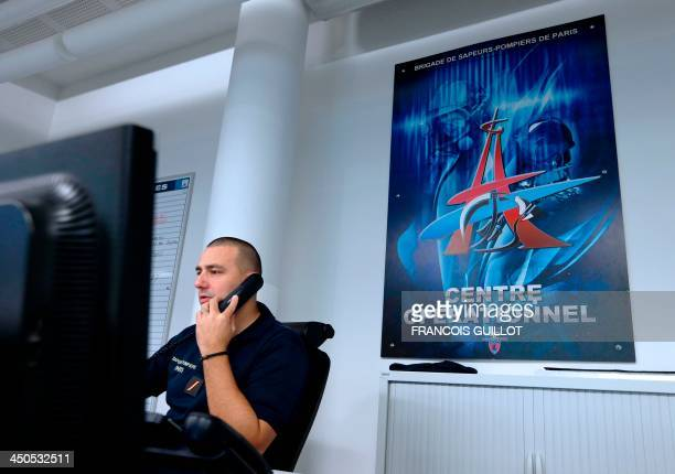 A firefighter works in a call centre at Paris fire brigade's operational centre in the Champerret fire station on November 19 2013 AFP PHOTO /...