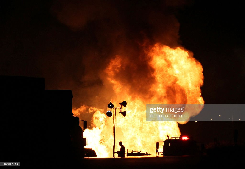A firefighter works next to flames caused by the explosion of a gas pipeline in Zapotlanejo, 30 km from Guadalajara city, Jalisco State, Mexico on October 19, 2012. The explosion injured two people and forced the evacuation of 600 residents, according to local authorities. AFP PHOTO/Hector Guerrero